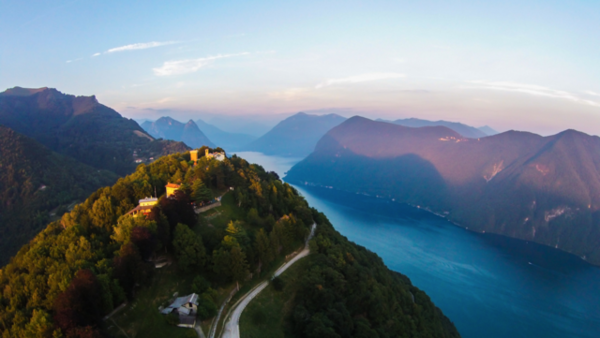 A warm glowing sunset over Monte Bre's summit, seen from a drone.  Lugano, Switzerland.