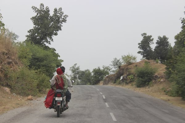 An indian man and his wife on a bike on the kumbhalgarh fort road, india.  (Photo Credit: MBS Photography)